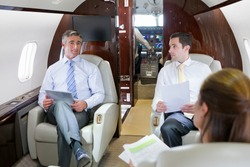 Business employees sitting in a private jet and having a meeting