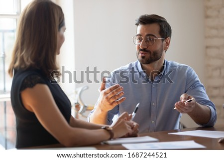 Business entities gathered together for negotiations, meeting lead by Caucasian businessman team leader express opinion point of view. Businesspeople sit at desk in boardroom solving issues concept