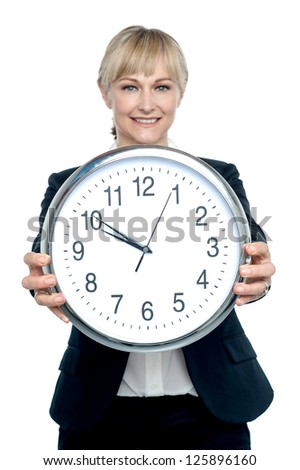 Business executive displaying big wall clock which strikes 9:50