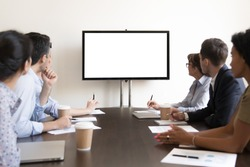 Business executive people group sitting at conference table looking at white blank mockup tv screen on wall watching presentation in meeting room, company training corporate team seminar in boardroom