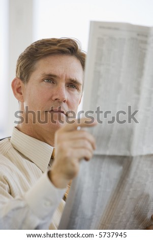 Business executive reading financial newspaper