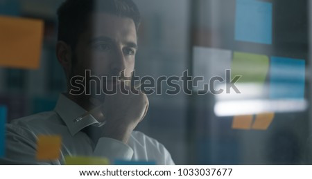 Business executive reading sticky notes on a glass, he is thinking about creative business solutions and strategies Foto d'archivio ©