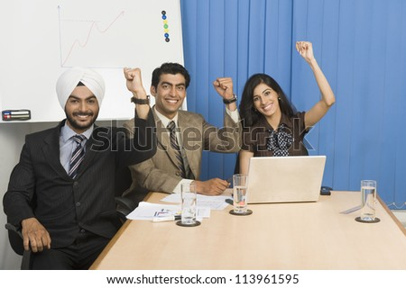 Business executives raising hands in an office