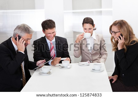 Business executives sitting around a table enjoying a relaxing cup of coffee together during a break