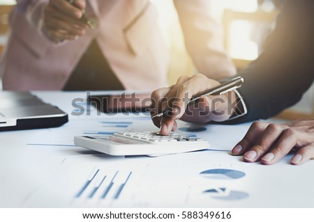 business executives working on calculator with data document at the office