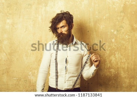 Business fashion and beauty. Fashion model with stylish hair. Guy or businessman at textured wall. Man with long beard and mustache on face. Hipster in shirt and suspenders. #1187133841