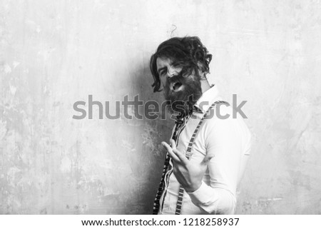 Business fashion and beauty. Fashion model with stylish hair. Guy or businessman at textured wall. Man with long beard and mustache on shouting face. Hipster in shirt and suspenders with musical tie. #1218258937