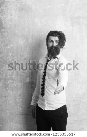 Business fashion and beauty. Fashion model with stylish hair on textured wall background Guy hold hand for handshake. Man with long beard and mustache on happy face. Hipster in shirt and musical tie. #1235355517