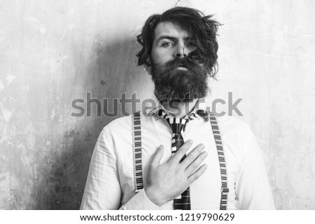 Business fashion and beauty. Guy or businessman at textured wall. Man with long beard and mustache on face. Fashion model with stylish hair. Hipster in shirt and suspenders with musical tie. #1219790629