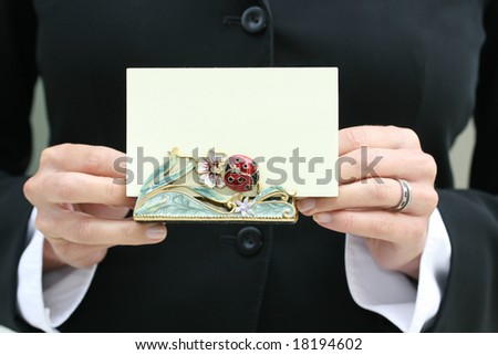 """Business female in a suit holding a blank business card, notecard. Excellent for communication, """"contact us"""" or """"email us"""" theme."""