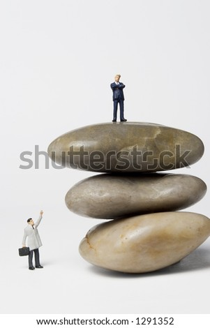 Business figures with rocks