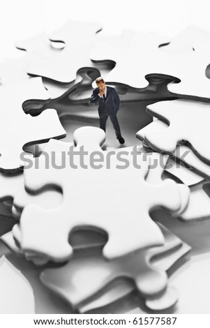 Business  figurine in pile of white jigsaw puzzle pieces
