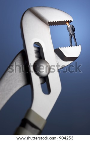 Business figurines in a clamp / blue background and spotlight