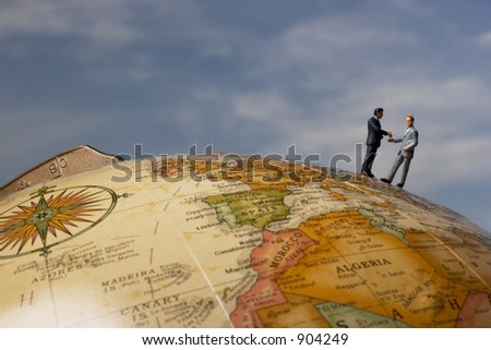 Business figurines on earth globe shaking hands with clouds
