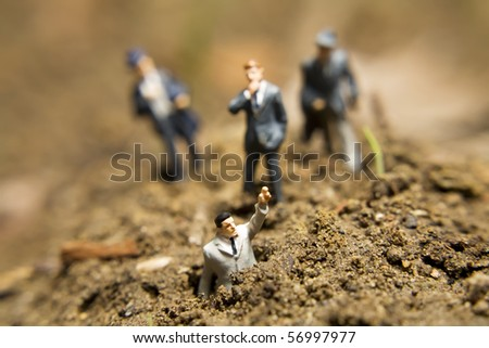 Business figurines placed outside in the dirt