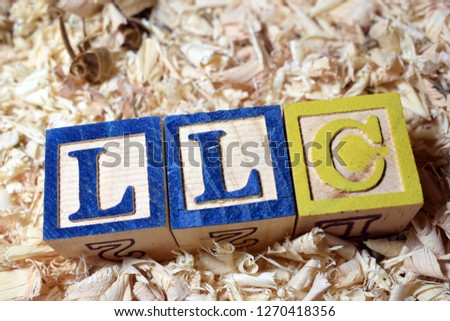 Business finance acronyms placed in a wooden block behind wooden saw dust #1270418356