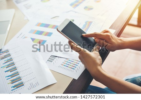 Business finance and business people use smartphones with paper graph stock at the office. Network internet of things concept. #1427572301