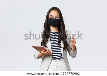 Business, finance and employment, covid-19 preventing virus and social distancing concept. Smiling real estate broker wearing protective mask during meeting, pointing camera, hold digital tablet