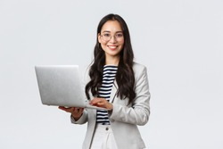 Business, finance and employment, female successful entrepreneurs concept. Confident smiling asian businesswoman, office worker in white suit and glasses using laptop, help clients