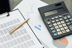 Business financial documents, office calculator and pen on the table. Numbers and graphs. Black table