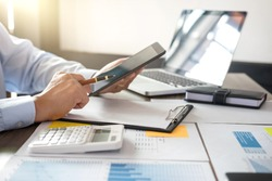 Business Financing Accounting Banking Concept, businessman using tablet and doing finances, calculate about cost to real estate investment and in other, tax system.