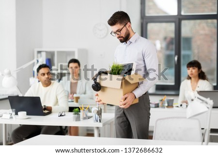 business, firing and job loss concept - fired male office worker with box of his personal stuff and his sad colleagues