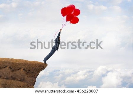 business freedom concept courageous daring businessman flying off a cliff holding faith in balloons