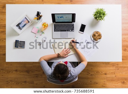 business, freelance and people concept - woman with laptop computer writing to notebook at office #735688591