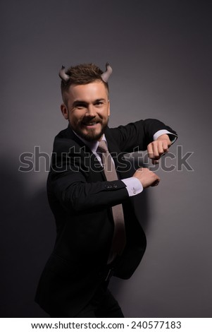 Business games.  Devilish cunning businessman with horns on head in full suit dancing and smiling happily against grey background