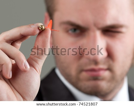 Business games - young businessman aiming by dart