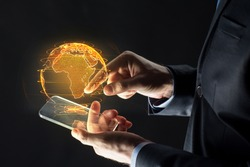 business, globalization and future technology concept - close up of businessman hands with transparent smartphone and earth hologram over black