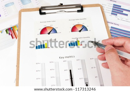 Business graph printed on the white paper with a hand holding a pen on it