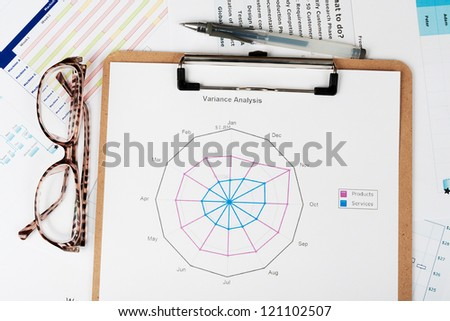 Business graph printed on white paper  with pen and glasses