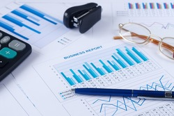 business graph, sales report, calculator, pen and eyeglasses