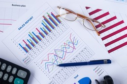 business graph, sales report, calculator, pen and glasses, top view