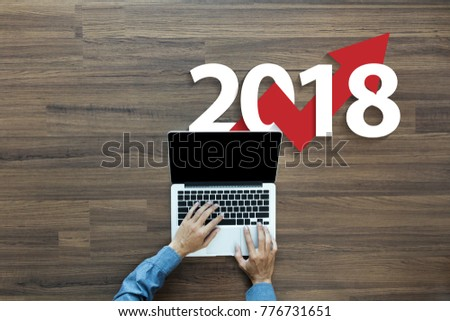 Business graph with arrow up and 2018 symbol, Success concept and growth idea concept, With businessman working on laptop computer PC, Top view from above