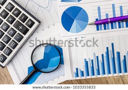 Business graph with magnifying glass and calculator pen on table #1033355833