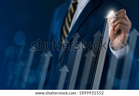 Business growth, boost up business, progress in business or success concept. Businessman is drawing raising arrow graph on dark tone background.