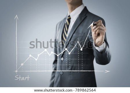 Business growth, progress or success concept. Businessman is drawing a growing graph on bright tone background.