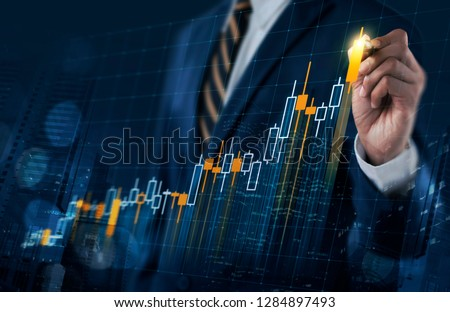 Business growth, progress or success concept. Businessman is drawing a growing virtual hologram stock bar chart on dark blue background.