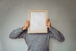Business Guy hides his face with a picture frame - Concept for marketing, target audience determination, buyer persona