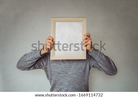 Business Guy hides his face with a picture frame - Concept for marketing, target audience determination, buyer persona Foto stock ©