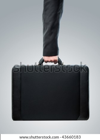 Business Hand and arm holding brief case over a gray radial gradient background