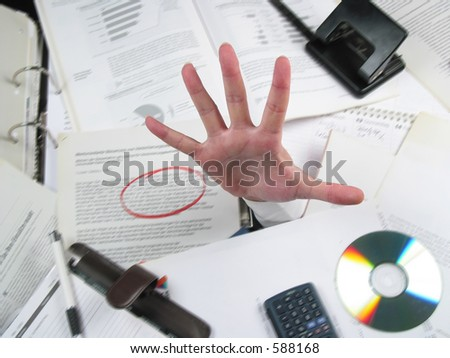 Business hand coming out of a pile of work on an office desk expressing need of help! Hand is focused and sharp, background is motion-blurried.