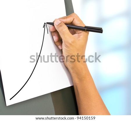 Business hand drawing a rising arrow, representing business growth.