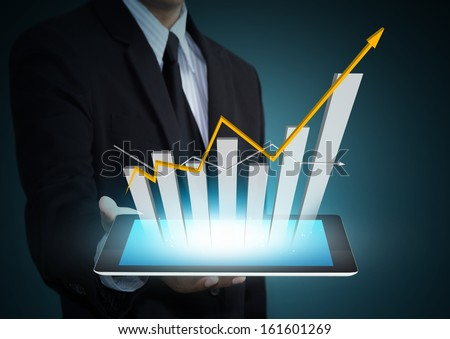 Business hand holding growth chart on tablet technology - stock photo