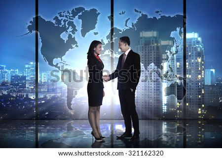 Business hand shake over world map background #321162320