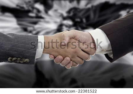 Business Hand shaking on a word map background