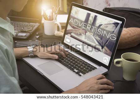 business hand typing on a laptop keyboard with Advertising homepage on the computer screen branding commerce concept.