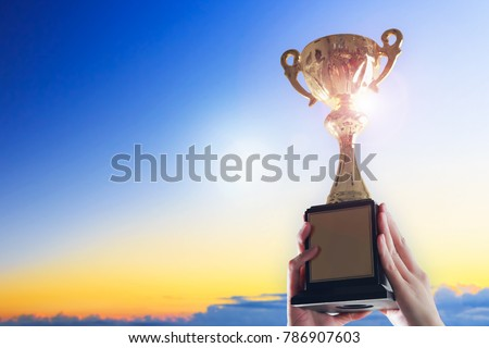 Business hands holding trophy cup on sky background. #786907603